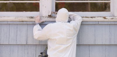 A house painter in a hazmat suit scrapes off dangerous lead paint from a window sill