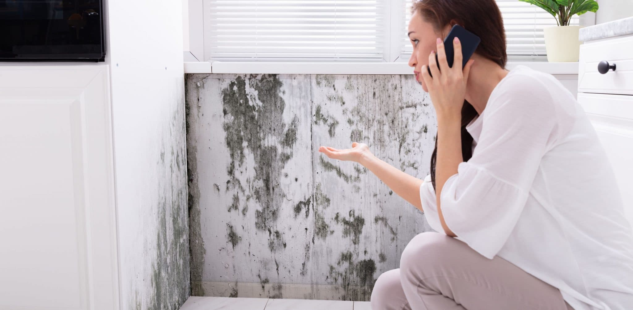 Woman on the phone in front of mold covered wall